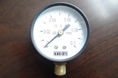 A pressure gauge is on the table.